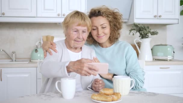 Smiling Grandmother And Granddaughter Taking Selfie Photo On Smart Phone.