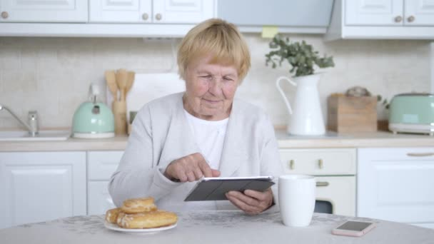 Grandmother Using Tablet Computer On Kitchen.