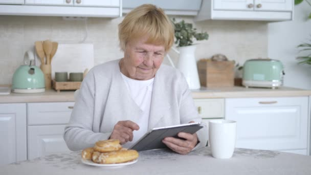 Elderly Woman Using Tablet At Home Resting On Kitchen.