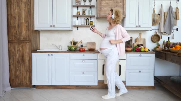 Happy Healthy Pregnancy Concept. Pregnant Woman Dancing On Kitchen With Smartphone.