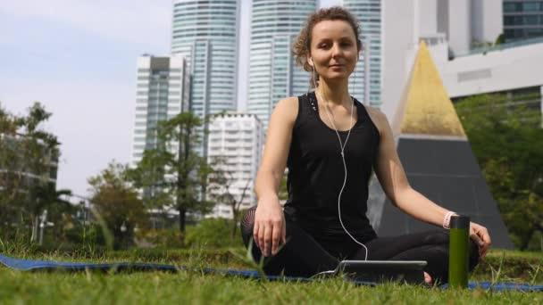 Klidná žena dělá jógu pomocí tabletu ve sluchátkách v parku