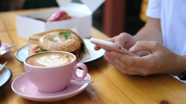 Közelkép a nők kezét a mobil okostelefon ül a kávézóban egy csésze kávé