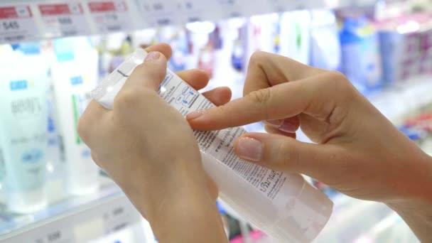 Female Customer Reading Label on Cosmetic Bottle In Supermarket