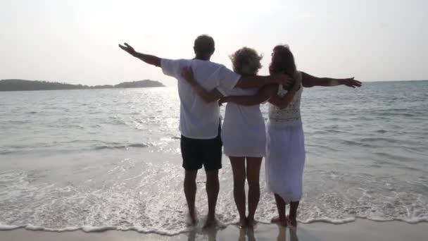 Šťastná pozitivní rodina s pažemi roztažené při pohledu na moře na pláži