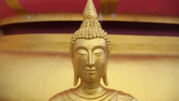 Detailní záběr na tvář sochy zlatého Buddhy v Thajsku
