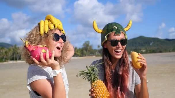 Cheerful Women Friends in Funny Fruit Hats on Beach
