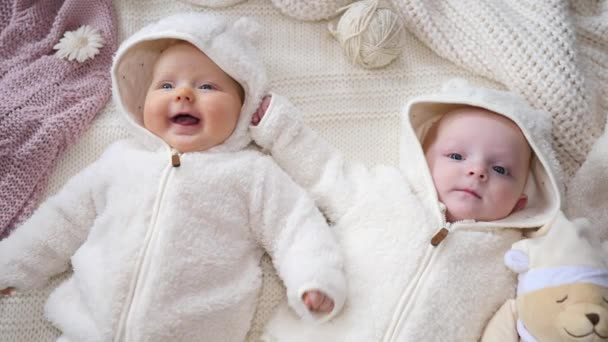 Smiling Cheerful Twins Babies Lying On Knitted Blanket.