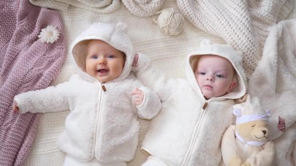 Dvě sladké děti ležící na pletenou přikrývku