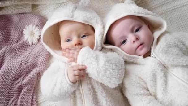 Dvě dětská dvojčata ležící spolu v posteli v béžových útulných bundách. Podzimní zimní sezóna.