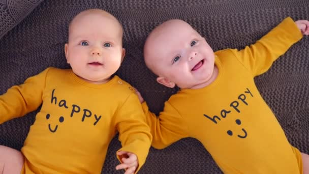 Twin Babies Wearing Happy Ochre T-Shirts And Lying On Knitted Blanket. Top View.