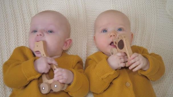 Twin miminka hrát s dřevěnou Eco hračky nošení pletených Ochre svetry.