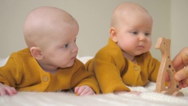 Dvojčata ležící na břiše a hrající si s dřevěnou Eco hračkou. Udržitelnost, koncepce zdravotní péče.