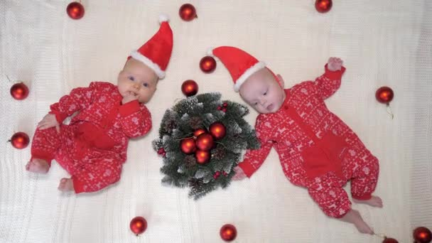 Twin Babies In Christmas Hats Lying Together On Knit Blanket. Xmas Concept.