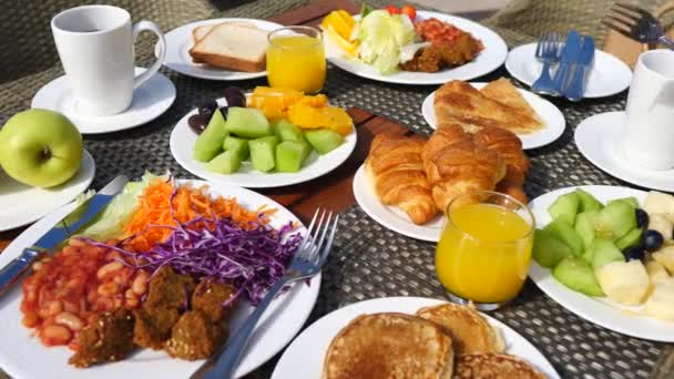 Žena snídá s pomerančovým džusem, ovocem, palačinkami a croissanty.