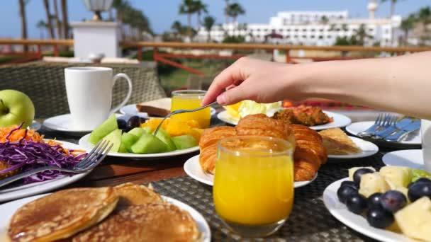 Reggeli az asztalon narancslével, gyümölcslével, palacsintával és croissanttal. Közelkép.