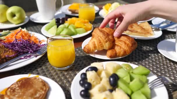 Chutná snídaně na stole s pomerančovým džusem, ovocem, palačinkami a croissanty.