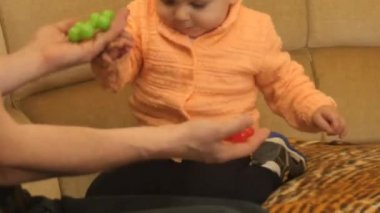 cute active 9-10 months old baby boy making choice between red and green toys - smooth zoom