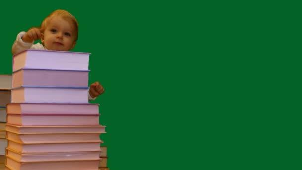 Cute usmívající se 1 rok staré dítě stojící poblíž knihy hromadu zelená obrazovka