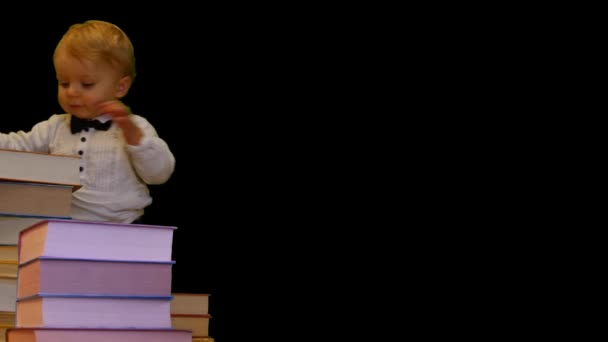 cute 1 year baby supports on pile of books on black background