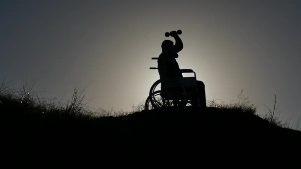 Behinderter Mann im Rollstuhl macht Turnhalle Übung Silhouette Zeitlupe nähert sich Kamera