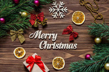 Merry Christmas title on the luxurious wooden table surrounded with christmas present, slices of lemon, bells and other christmas tinsel