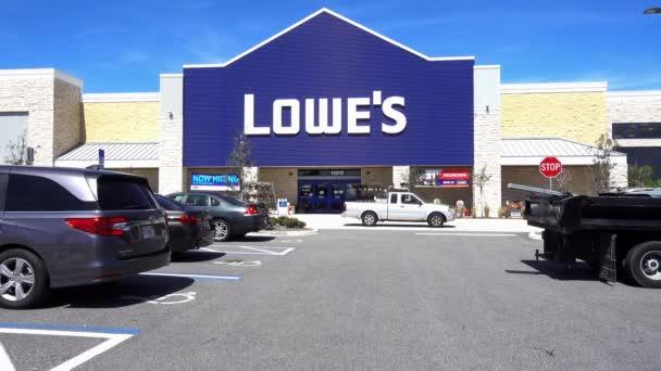 Orlando, FL / USA - 5 / 8 / 20: A Lowes Home Improvement hardveráruház kültéri boltja autókkal és a boltba sétáló emberekkel.