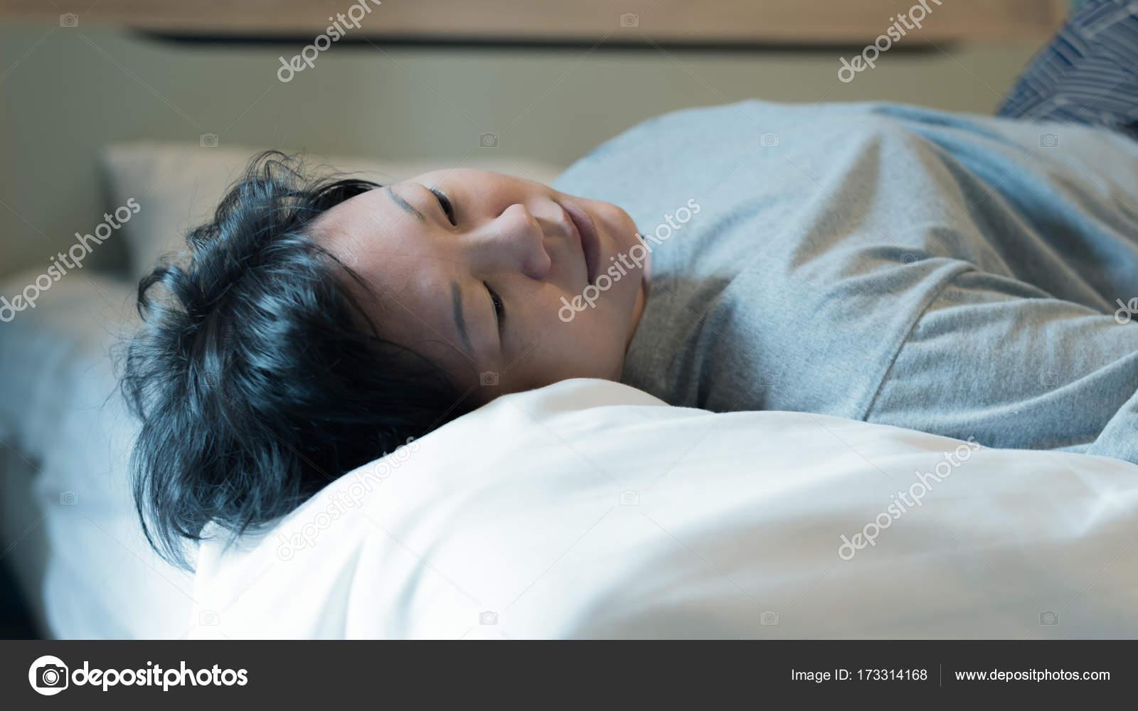 Asiatische Frau ein Nickerchen oder schlafen im Bett im Schlafzimmer ...