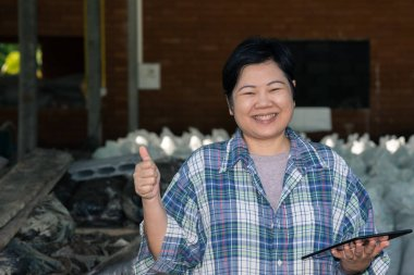 Asian woman smart farmer agriculturist happy at a Fertilizer composting plant with Organic Fertilizer, Compost (Aerobic Microorganisms) from animal waste for use in the organic agriculture industry