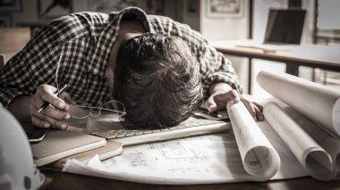 tired engineer lying on blueprint