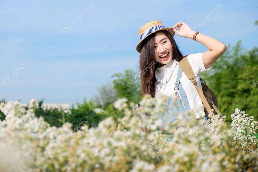 Pretty hipster asian teen girl in a spring white flower garden,