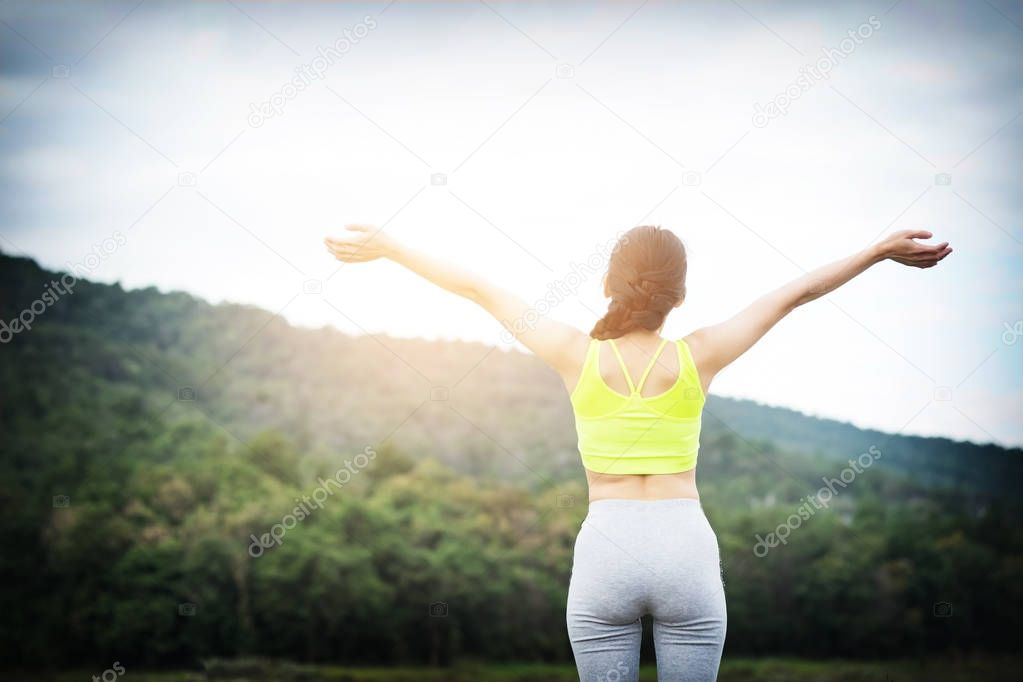 Relaxed woman breathing fresh air raising arms.