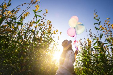 Girl running on the field of yellow flowerwith balloons at sunse