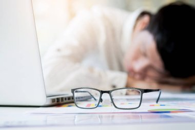 tired businessman sleeping while calculating expenses at desk i