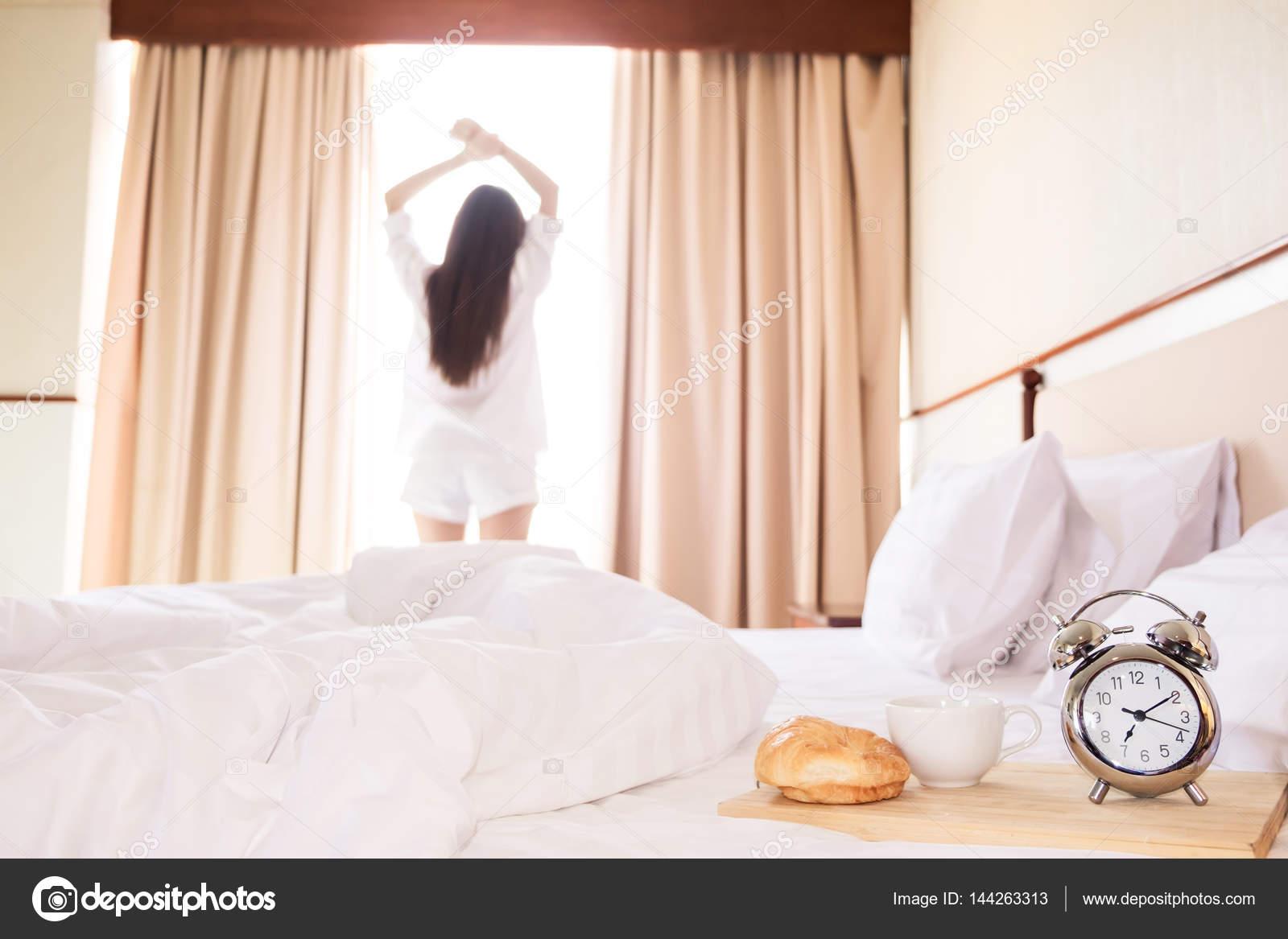 Bed Gordijn 5 : Gezonde vrouw die zich uitstrekt in bed kamer en open de gordijnen