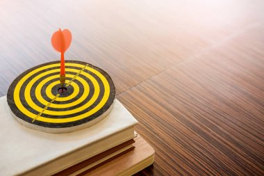 Little Dartboard with dart on books