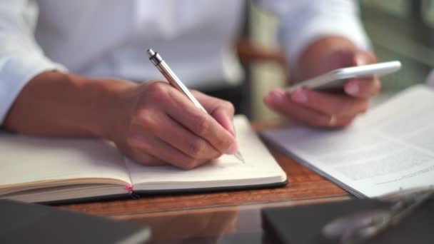 4k video of man hand holding pen writing to do list or business data  with pen at notebook dairy.