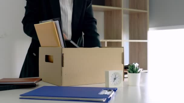 4k video of Businessmen packing up all for personal belongings and files into a brown cardboard box resignation from the company, job placement and vacancies concept