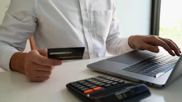 4k-Video der Hände mit Kreditkarte und Laptop im Home Office, Zahlungs- und Online-Shopping-Konzept