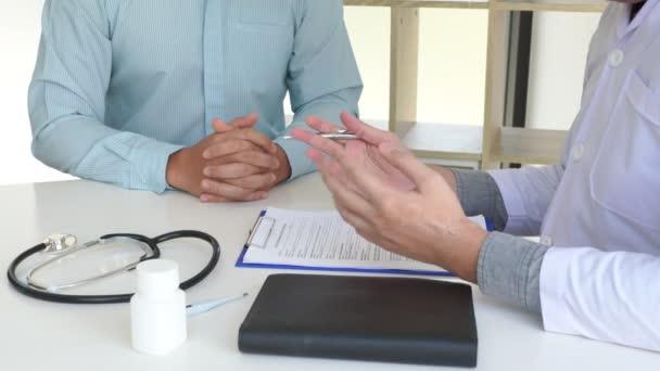 4k video pacienta, jak pozorně naslouchá doktorovi, který vysvětluje symptomy pacienta, nebo klade otázku, když spolu diskutují o papírování v konzultaci
