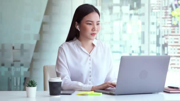 4k videó Boost hangulat a munkahelyen. Vidám ázsiai nő zenét hallgat vezeték nélküli fülhallgatóval énekel és táncol vidáman az irodában. szórakozni.