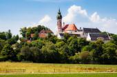 Fotografie Landschaftlich reizvoller Blick auf das alte idyllische Kloster Andechs mit historischem Kirchturm und berühmter Brauerei auf einem Hügel an einem schönen sonnigen Sommertag mit blauem Himmel, Landkreis Starnberg, Oberbayern, Deutschland