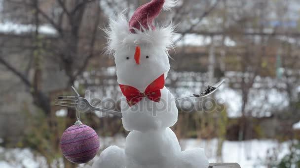 Sněhulák, první sníh, na sobě k Vánocům. Taje a klesá.