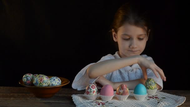 Girl playing Easter eggs in trays.