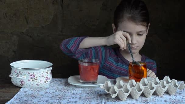 Krásná holčička maluje vajíčka na Velikonoce, červené a žluté