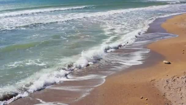 Homokos strand óceáni szökőárral összeomlik egy homokos strandon fröccsenő. Légi drón videó