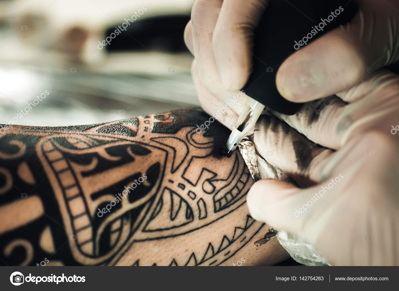 Master Tattoo Artist In Gloves Makes Tattoo On Hand Men Stock