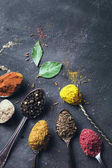 Beautiful colored spices in a silver spoon on a dark background. The concept of cooking, healthy food