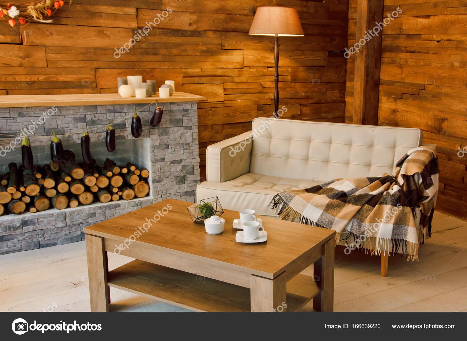 Fauteuil bij de open haard met brandhout u stockfoto