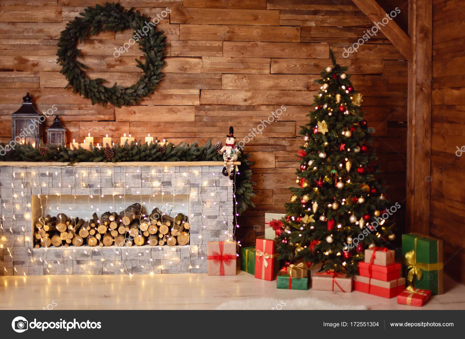 Foto des Interieurs der Zimmer mit einer Holzwand, Kranz und Girlanden,  Weihnachtsbaum, Kamin mit Brennholz. Weihnachtliche Atmosphäre.