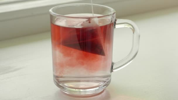 Red tea in teabag brewing in water. Close up